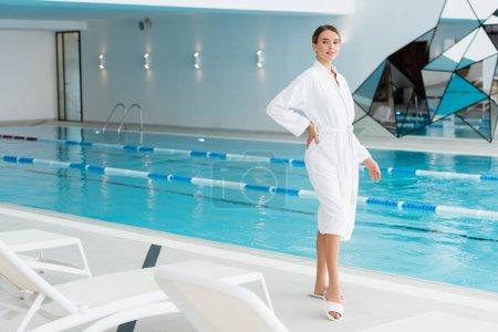 Photo pour Longueur pleine de femme heureuse en peignoir debout avec la main sur la hanche près de la piscine dans le centre de spa - image libre de droit