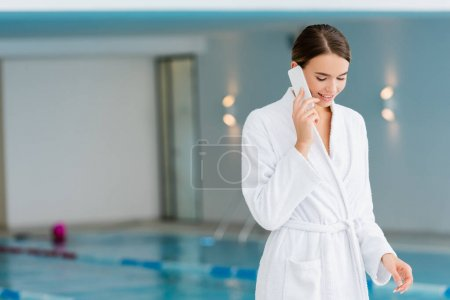 cheerful young woman in white bathrobe talking on smartphone in spa center
