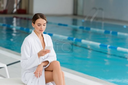 young woman in white bathrobe sitting on deck chair and holding smartphone in spa center