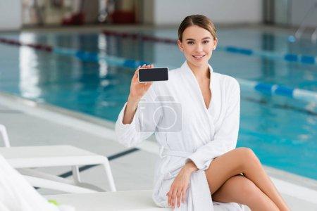 mujer joven y complacida en albornoz blanco sosteniendo teléfono inteligente con pantalla en blanco en el centro de spa