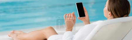 young woman resting on deck chair and holding smartphone with blank screen in spa center, banner