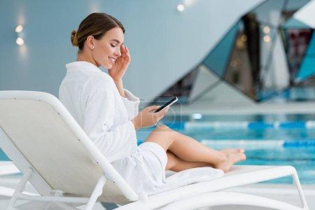mujer feliz descansando en la silla de cubierta y sosteniendo el teléfono inteligente cerca de la piscina