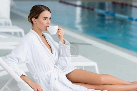 Photo for Young woman drinking tea while sitting on deck chair near swimming pool on blurred background - Royalty Free Image