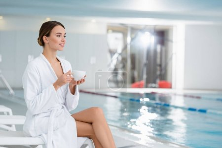 Smiling woman with cup sitting near swimming pool on blurred background in spa center