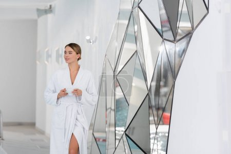 Photo for Young woman in bathrobe holding cup in modern spa center - Royalty Free Image