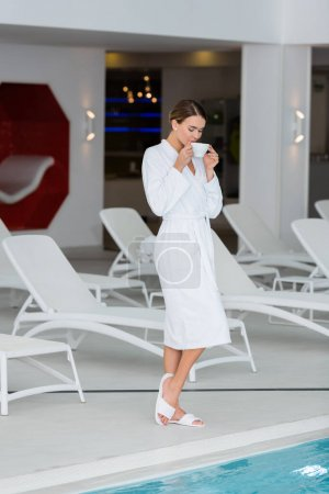 Young woman in white bathrobe and slippers holding cup near swimming pool in spa center