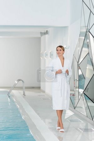 Photo for Happy woman in bathrobe holding cup while walking near swimming pool in spa center - Royalty Free Image