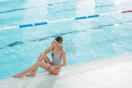 Sexy woman sitting near swimming pool in spa center
