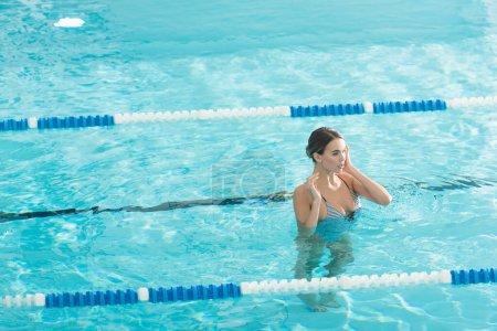 Photo pour Jeune femme en maillot de bain debout dans la piscine avec de l'eau ondulée - image libre de droit