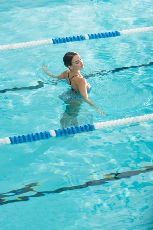 Woman relaxing while swimming in pool in spa center