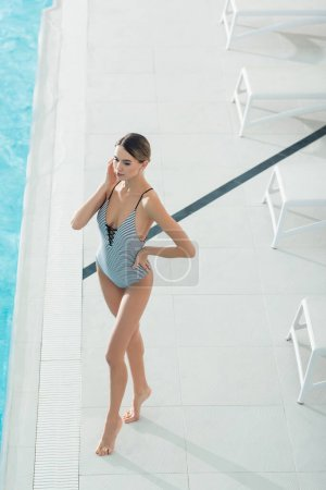 Photo for High angle view of young woman in swimsuit standing with hand on hip in spa center - Royalty Free Image