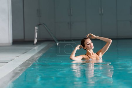 young woman with closed eyes swimming in pool of luxury spa center