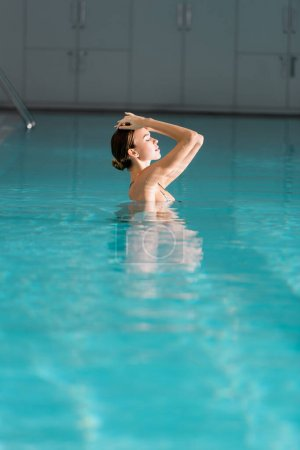 woman with closed eyes swimming in pool of luxury spa center