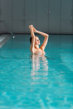pretty young woman swimming in pool of luxury spa center