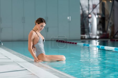 Photo for Young woman sitting in swimming pool with blue water - Royalty Free Image