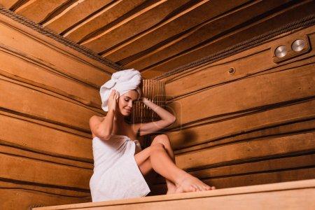 Positive Frau fixiert Handtuch auf Kopf in Sauna