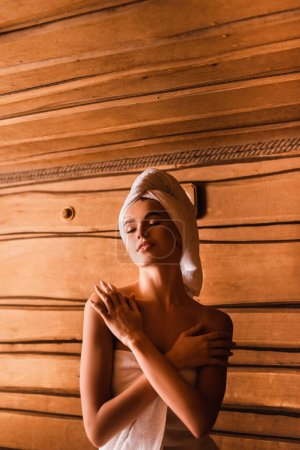 Pleased woman wrapped in towels relaxing in sauna