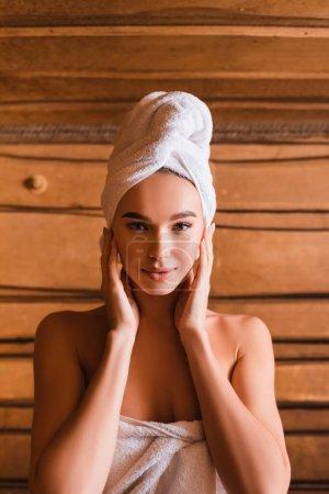 Młoda kobieta w białych ręcznikach patrzy na kamerę w saunie