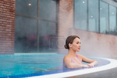 Young woman relaxing in swimming pool with hot water