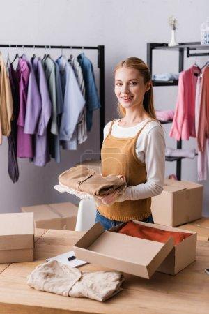 glückliche Geschäftsfrau mit Kleidern im Showroom in der Nähe von Kleiderbügeln auf verschwommenem Hintergrund