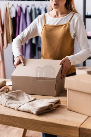 partial view of seller packing carton boxes in clothes showroom, blurred foreground