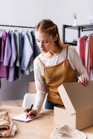 young seller writing order in notebook near carton package in clothes showroom