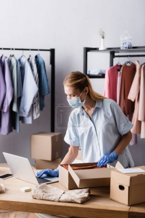 young businesswoman in medical mask, collecting order near laptop in showroom