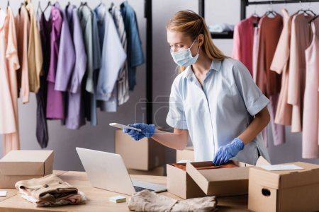 showroom owner in medical mask, working with laptop and smartphone near cardboard boxes