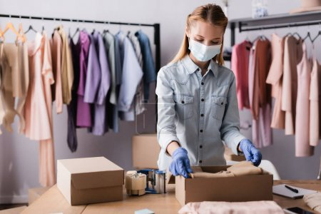 young businesswoman in medical mask, packing clothes into boxes in showroom, blurred foreground