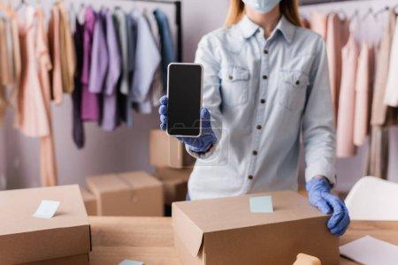 Ausgeschnittene Ansicht eines Showroom-Inhabers in Latexhandschuhen, der sein Smartphone in der Nähe von Schachteln im unscharfen Vordergrund hält