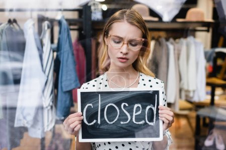 sad proprietor holding board with closed lettering in showroom