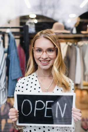 successful businesswoman holding board with open lettering in clothes showroom