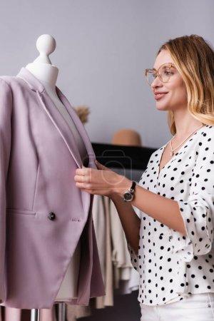 smiling showroom owner adjusting fashionable blazer on mannequin