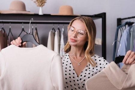 freudiger erfolgreicher Showroom-Besitzer hält Kleiderbügel mit Klamotten im verschwommenen Vordergrund
