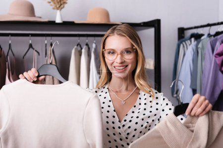 happy proprietor smiling at the camera while holding clothes on hangers in showroom