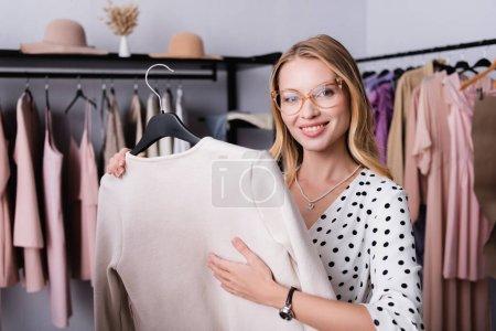modischer Showroom-Besitzer lächelt in die Kamera, während er Kleiderbügel mit Jacke hält