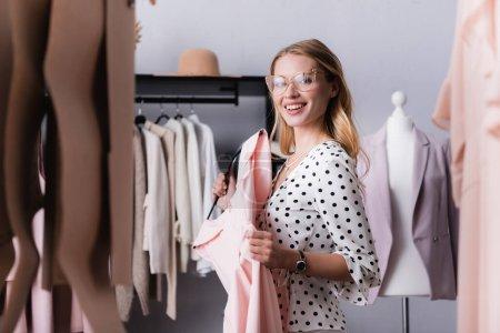 feliz elegante mujer de negocios sosteniendo vestido en sala de exposición en primer plano borrosa