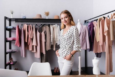 joyful showroom owner standing with hands in pockets near hangers with clothes