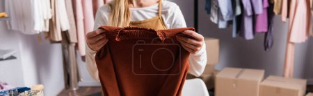 cropped view of showroom owner holding sweater, banner