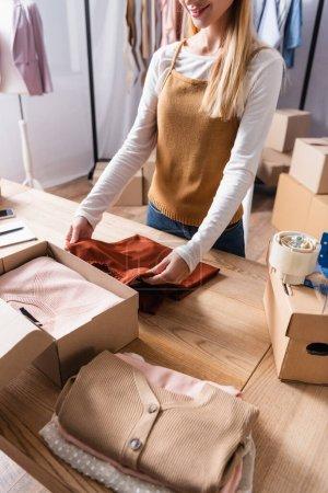 Teilansicht eines lächelnden Showroom-Besitzers, der Kleidung in Karton packt