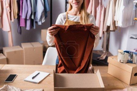 Teilansicht des Verkäufers, der Pullover hält, während er Bestellungen im Showroom abholt