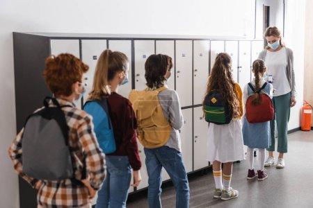 Photo pour Des écoliers portant des masques médicaux faisant la queue près du professeur avec un thermomètre infrarouge - image libre de droit