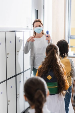 Teacher in medical mask holding infrared thermometer near pupils in queue on blurred foreground