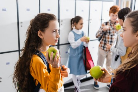 Photo for Schoolgirls holding apples near classmates on blurred background in corridor - Royalty Free Image