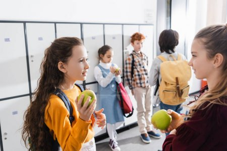 Smiling schoolgirl with apple and notebook talking to friend near classmates on blurred background