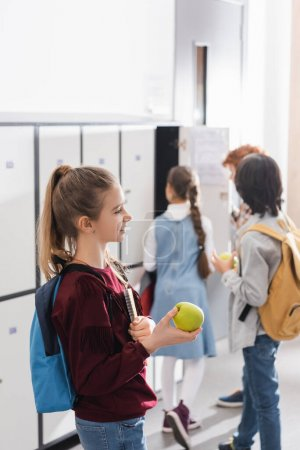 Cheerful schoolkid holding green apple and copybook near pupils on blurred background in hall