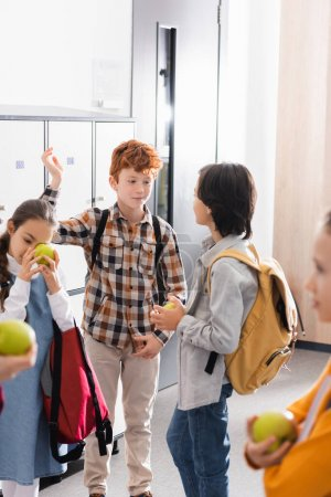 Schoolboy talking to friend with apple near friends on blurred foreground in school corridor