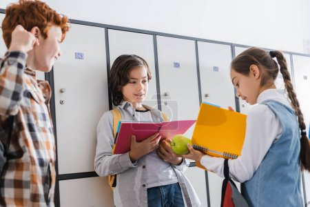 Girl looking at copybook while holding apple near classmates in hall