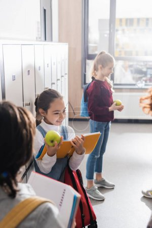 Happy kid holding apple and open notebook near friends on blurred foreground in school
