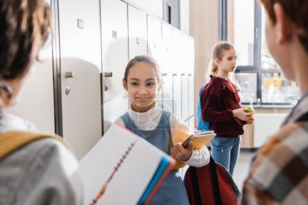 Schoolgirl with notebook smiling at friends on blurred foreground in school hall
